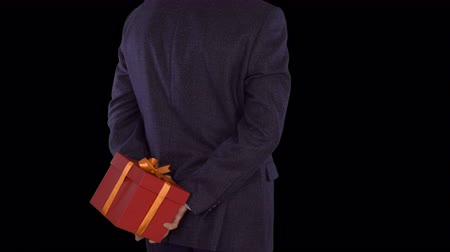 cavalheiro : A man in a business suit is holding a red gift box behind his back. Caucasian man shifts from foot to foot. Businessman gives a gift. Close up locked down shot. Alpha channel chroma key. Back view. Stock Footage