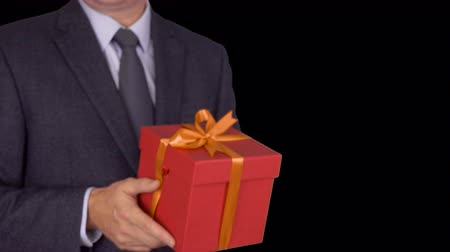 фокус : Caucasian businessman hold and give red gift box. From unfocus to focus motion. Adult man in classic business suit hold red gift box. Alpha channel chroma key transparent background. Locked down.