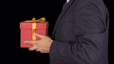 cavalheiro : A businessman in a suit gets a present. The man received a red gift box for the holiday. The businessman was given a red gift box. Award to a businessman. Alpha channel chroma key.