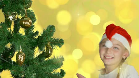 świety mikołaj : Happy young girl dancing near christmas tree in Santa red hat. Happy young caucasian girl indoors studio close up shot. Golden background. Decorated christmas tree.
