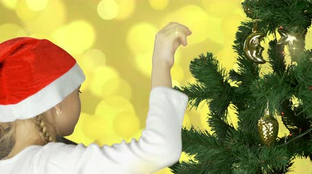 ladin : Young caucasian girl in red Santa hat decorate green christmas tree with golden sphere ball. Prepairing to celebrate Merry Christmas and Happy New Year. Abstract gold flickering lights background.
