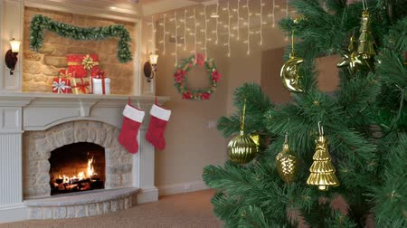 украшенный : House living room decorated for Christmas celebrate. Christmas holiday eve. Green fir tree with gold decor. Flame in fireplace. Gift box with gifts for family. Lifestyle concept New Year. Sound., Стоковые видеозаписи