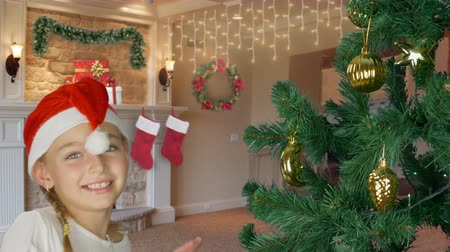 świety mikołaj : Happy young girl dancing near christmas tree in Santa red hat. Happy young caucasian girl indoors close up. Decorated christmas tree. Christmas decorated interior home living room.