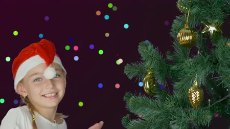 świety mikołaj : Happy young girl dancing near christmas tree in Santa red hat. Happy young caucasian girl close up. Decorated christmas tree. Colorful background with shyning color dots circles lights flickering.