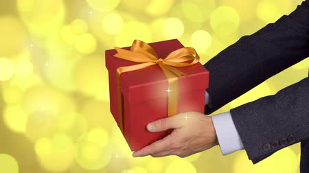 mech : Two male hands holds red gift box with gold bow. Celebrate eve present gift box. Caucasian man in classical suit. Gold lights background. Locked down.