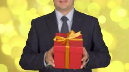 cavalheiro : A man in a business suit with a tie is holding a red gift box. A man gives a gift. A businessman with a gift in his hands. Abstract background gold flash flickering and glow circle lights bokeh.