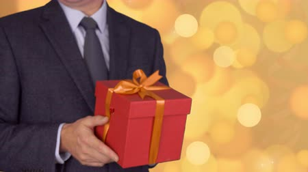 фокус : Caucasian businessman hold and give red gift box. From unfocus to focus motion. Adult man in classic business suit hold red gift box. Abstract background gold flash flickering glow circle lights bokeh Стоковые видеозаписи