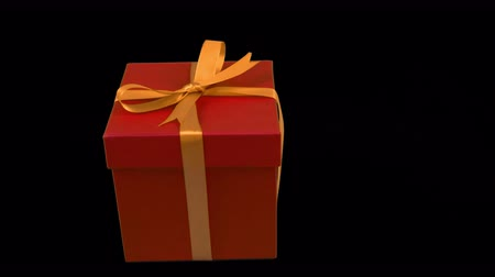 ajándékdobozban : Red gift box with yellow gold ribbon bow rotate at transparent background. Alpha channel chroma key transparent background. Have empty space for text. Pan.