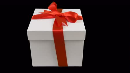 градация : White gift box with red ribbon bow stands at black background. Track to right. Empty space for text. Стоковые видеозаписи