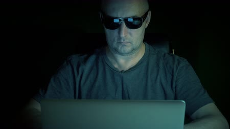 senha : Man sits with laptop and surf internet. Man coding at computer. Hacker dark night. Low key.