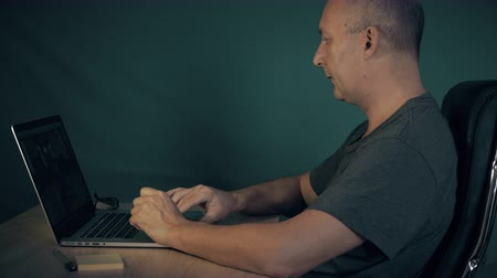 watching : Man browse internet at laptop computer. Man surfing internet sits at table late evening night. Student looking for information in network. Film look side view. Stock Footage