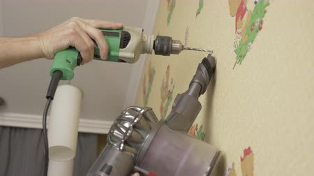 broca : Adult caucasian man drilling the wall at home with electric drill. Close up locked down shot. Low angle. Diy man use vacuum cleaner.