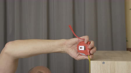 medir : White man with roulette measure the bookshelf. Furniture DIY construction. Stock Footage
