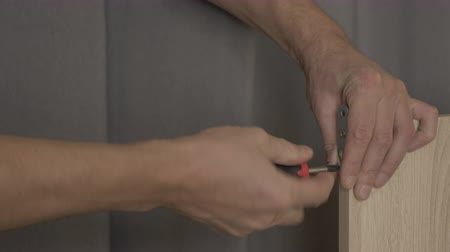 undo : Man unscrew the screw from wooden furniture bookshelf. Close up male hands with screwdriver.
