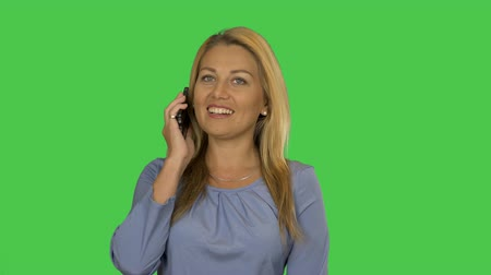 мобильный телефон : Attractive blonde businesswoman talking on mobile phone with client. Alpha channel. Стоковые видеозаписи