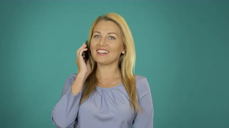 szőke : Adult caucasian girl speaks by cell phone and smiling. White blonde female use phone for conversation communication.