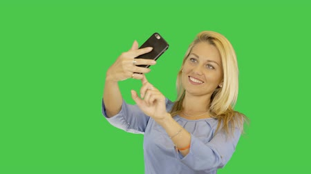 selfie girl : Blonde young women make selfie on a smartphone. Caucasian girl taking pictures on smartphone. Alpha Channel transparent background. Copy space. Stock Footage