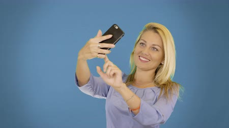 selfie girl : Portrait of excited cheerful smiling young pretty woman making selfie photo on smartphone. Solid background.