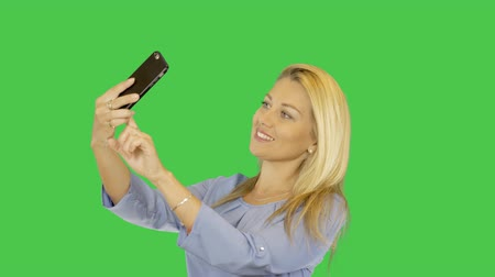 selfie girl : White blonde young girl smiling and make photo selfie on smartphone. Alpha channel transparent background. Stock Footage