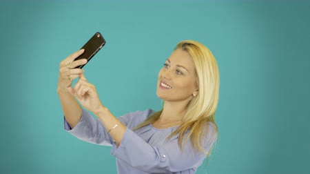 selfie girl : Young women make selfie on smartphone. Cute blonde girl make photo ob camera of cell phone. Copy space. Stock Footage