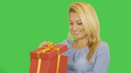 jóquei : Happy young women get red gift box and look inside. Girl is happy to receive the desired gift. Alpha channel keyed green screen