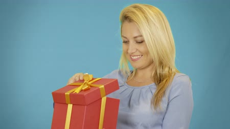 kutu : Wondered cute blonde young woman opening red gift box over blue background Stok Video