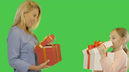 jóquei : Mom and daughter give gifts to each other. Mother and Daughter celebrate. Mom and daughter give presents together. Alpha channel keyed green screen. Stock Footage