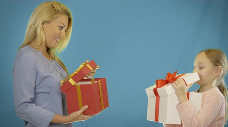adorável : Mom and daughter give gifts to each other. Mom gives the daughter a gift box. My daughter gives me a present.