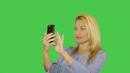 make photo : Blonde young woman is taking photo self portrait on a smartphone transparent green screen background. Alpha channel.
