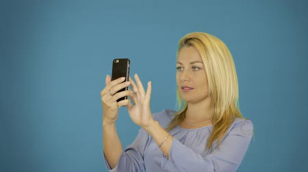 make photo : Young caucasian woman take photo on smartphone. Solid blue background. Female portrait waist up. Pretty blonde smiling. Stock Footage