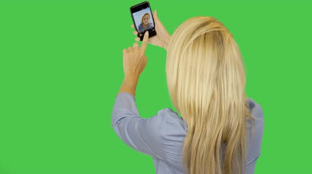 oneself : Young woman make selfie on smartphone. Blonde girl stands back rise up hand with camera and self portrait photography.