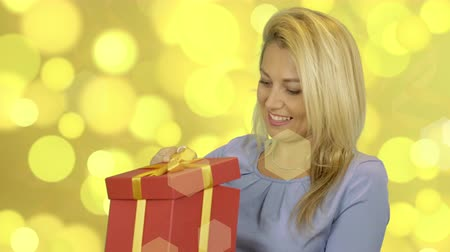 szőke : Excited cheerful attractive young woman in blue dress opening gift over gold background Stock mozgókép