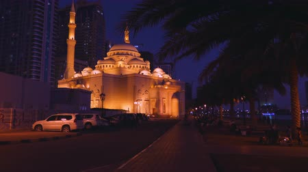 hijri : Move the camera to a beautifully lit mosque at night along the alley.