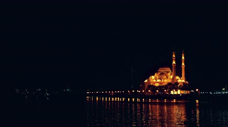 mussulman : Night view og Khalid lake with Emirates flag and Al Noor mosque illuminated with golden light. Chain of gold lanterns at waterfront. Stock Footage