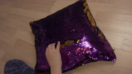 pisos : Hands of little girl writing word love on decorative pillow with sequin fabric Stock Footage
