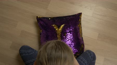 pisos : Baby hands drawing heart shape on decorative pillow with sequin fabric. Top view.
