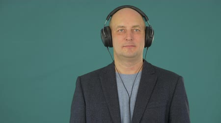 earpiece : A man in a business suit listening to music on headphones. A man enjoys the sounds of music.