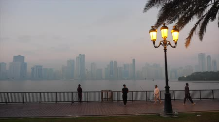 mussulman : Sharjah, United Arab Emirates - January 15, 2018. Morning or evening at quay. Man in white clothes runs. Fishermans on embankment. Beautiful lantern lights yellow. Skyscrapers at background.