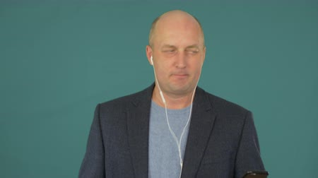 гаджет : Bald middle aged businessman listening music with earphones and smartphone