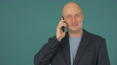 гаджет : Bald middle aged businessman smiling and talking on smartphone. Looking to camera.