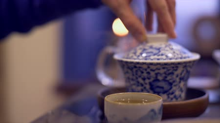 tigela : Male hands pouring hot water into bowl for brewing tea. Man hand taking tea cup Vídeos