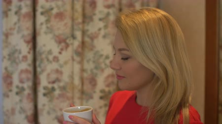 kufel : Woman drinking coffee at home. Portrait of happy blonde with mug in hands. Wideo