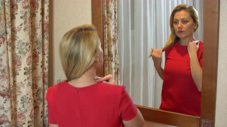 zmysłowy : Beautiful woman with blond hairstyle in red dress looking in mirror close up
