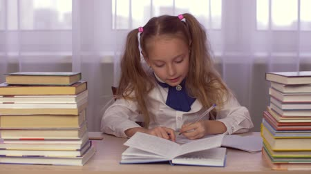 esquerda : School girl at table thinking about homework and writing in a school notebook Stock Footage