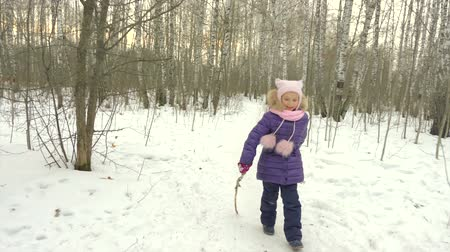 vigyorgó : Little girl runs through birch woods with a stick. Young girl happy jokes and falls to snow in winter forest.