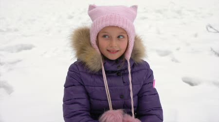 chapéu : Happy little girl smile and play with eyes. Young caucasian girl sits at snow at winter. Girl use snow ball maker outdoor. Vídeos