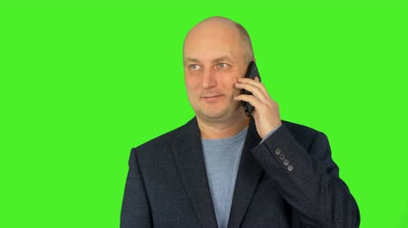 tenso : Successful businessman talking on cellphone Alpha channel, keyed green screen.
