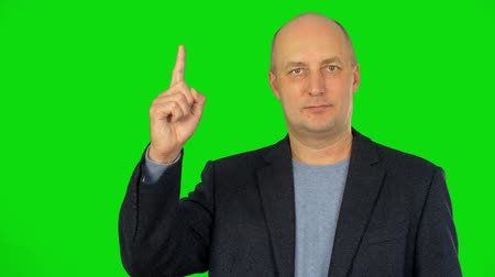 önemseme : A white caucasian man in a jacket raises his index finger up and smiles. Waist up portrait. Alpha channel, keyed green screen. Stok Video