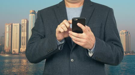 гаджет : Business man using mobile phone on background modern skyscrapers