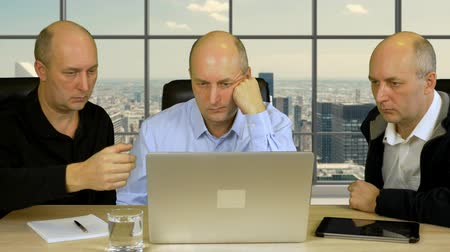 discutir : Three businessmen sit at table with laptop and discuss project. Modern office with panoramic windows and skyscrapers at background. Businessmen entrepreneurs solve problem.